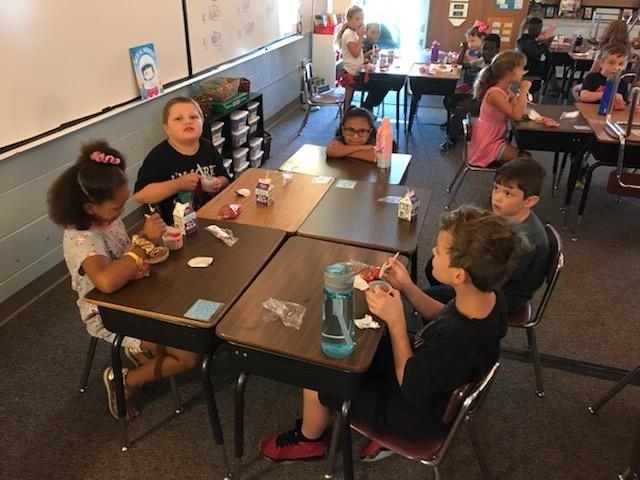 2nd grade enjoys Morning Meeting while eating their breakfast.